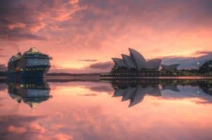 Sydeny opera house and cruise ship viewed across the harbour, sunset with clouds reflected on the water's surface